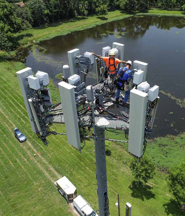 Tower climbers wave to the drone during an aerial tower inspection